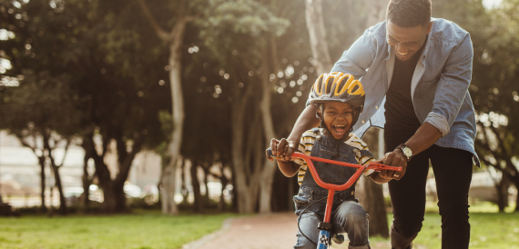 A father helping son ride bike outdoors